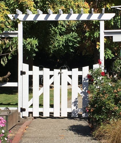 White arbor with gate, entry to back yard