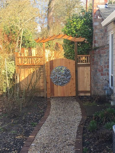 Cedar arbor and gate with artwork